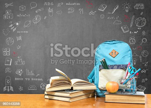 istock Back to school concept with school books, textbooks, backpack and stationery supplies on classroom desk with teacher's black chalkboard background with educational doodle for new academic year begin 992443058