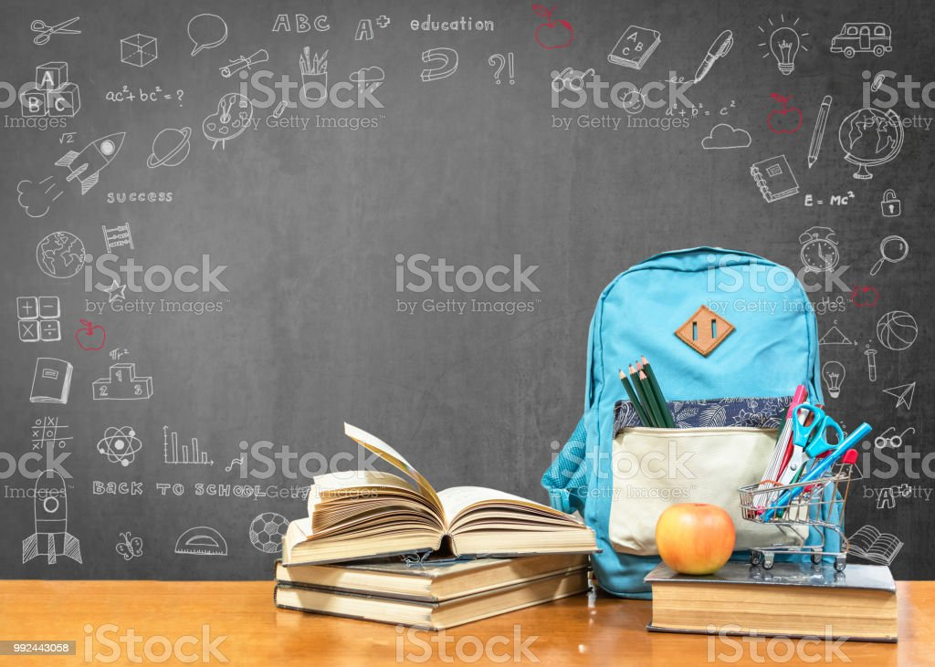 Back to school concept with school books, textbooks, backpack and stationery supplies on classroom desk with teacher's black chalkboard background with educational doodle for new academic year begin stock photo