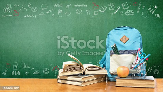 istock Back to school concept with school books, textbooks, backpack and stationery supplies on classroom desk with teacher's green chalkboard background with educational doodle for new academic year begin 999687132