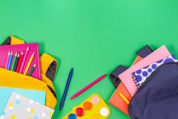 Zurück zum Schulkonzept. Gelbe und blaue Rucksäcke mit Schulmaterial, Bücher und Notizbücher auf hellgrünem Hintergrund. Ansicht von oben – Foto