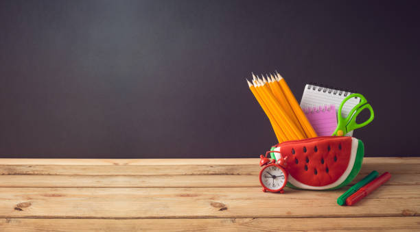 Back to school creative background with watermelon pencil case and school supplies on wooden table. stock photo