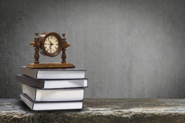 retour à la notion d'éducation scolaire avec horloge le livre sur le tableau noir - politique et gouvernement photos et images de collection