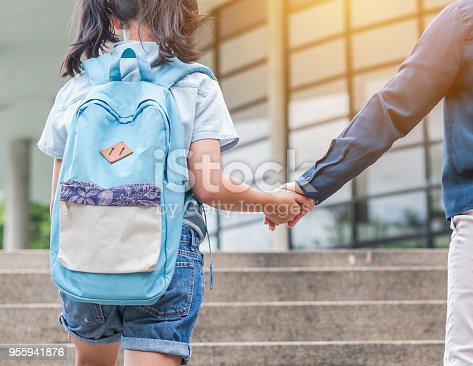 istock Back to school education concept with girl kid (elementary student) carrying backpacks holding parent woman or mother's hand walking up school building stair going to class 955941876