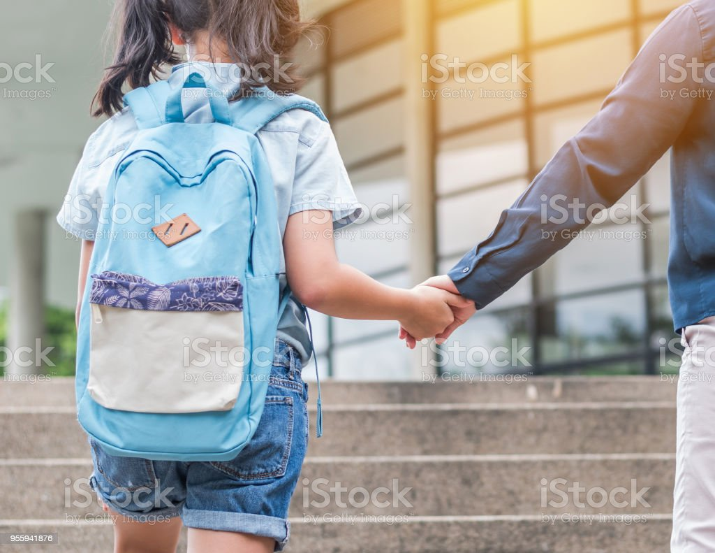 A concepto de Educación de la escuela con chico chica (estudiante de primaria) llevar mochilas con padres mujer o mano de la madre subiendo escalera de edificio de escuela va a clase - foto de stock