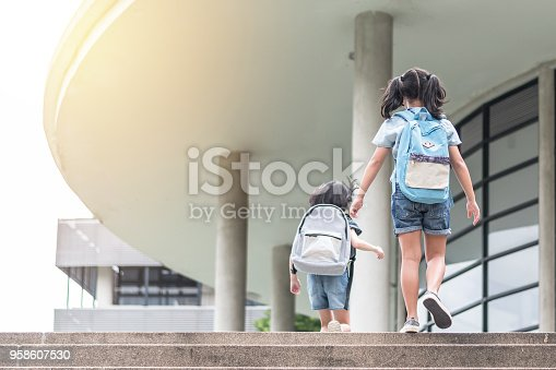 989255070istockphoto Back to school education concept with girl kids (elementary students) carrying backpacks going, running to class on school first day and walking up building stair happily 958607530