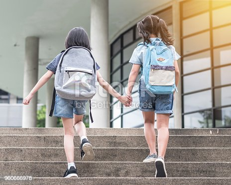 istock Back to school education concept with girl kids (elementary students) carrying backpacks going to class holding hand in hand together walking up school building stair happily 960666978