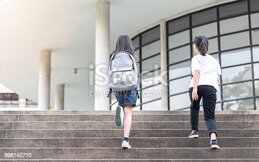989255070istockphoto Back to school education concept with girl kids (elementary students) carrying backpacks going, running to class on school first day and walking up building stair happily 998142710