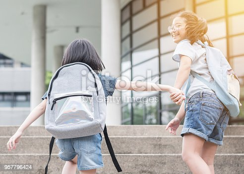 istock Back to school education concept with girl kids (elementary students) carrying big backpacks going to class holding hand in hand together, running and walking up school building stair happily 957796424