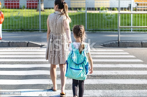 istock Back to school education concept with girl kids, elementary students, carrying backpacks going to class 1157981863