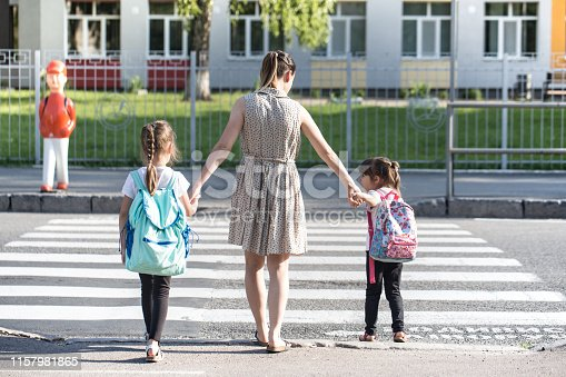 istock Back to school education concept with girl kids, elementary students, carrying backpacks going to class 1157981865