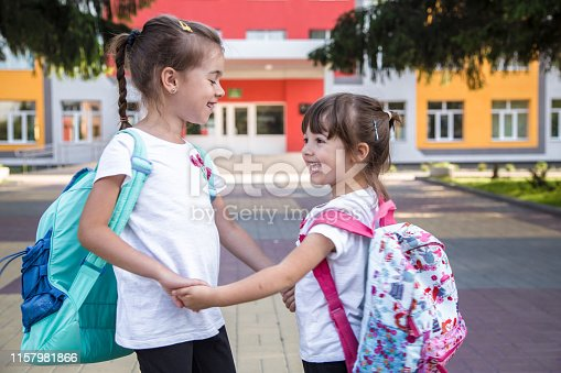 istock Back to school education concept with girl kids, elementary students, carrying backpacks going to class 1157981866