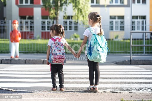 istock Back to school education concept with girl kids, elementary students, carrying backpacks going to class 1157981867