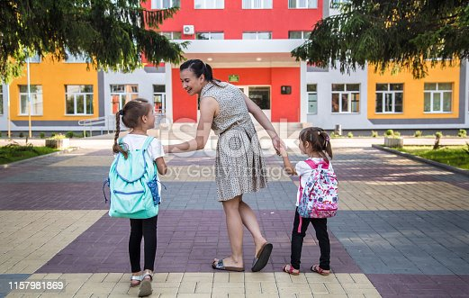 istock Back to school education concept with girl kids, elementary students, carrying backpacks going to class 1157981869