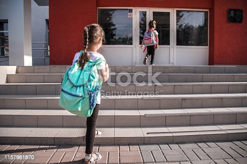 istock Back to school education concept with girl kids, elementary students, carrying backpacks going to class 1157981870