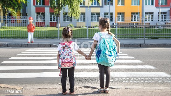 istock Back to school education concept with girl kids, elementary students, carrying backpacks going to class 1157981873