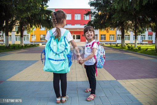 istock Back to school education concept with girl kids, elementary students, carrying backpacks going to class 1157981875