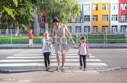 istock Back to school education concept with girl kids, elementary students, carrying backpacks going to class 1157981877