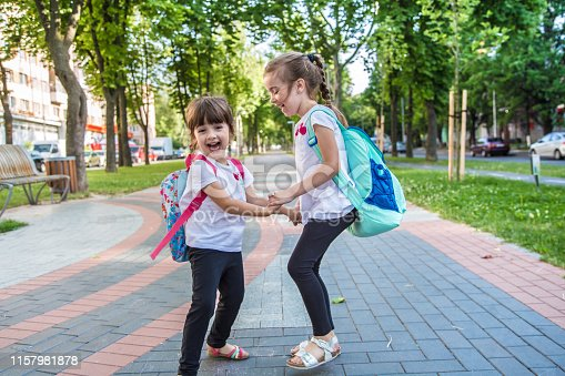 istock Back to school education concept with girl kids, elementary students, carrying backpacks going to class 1157981878