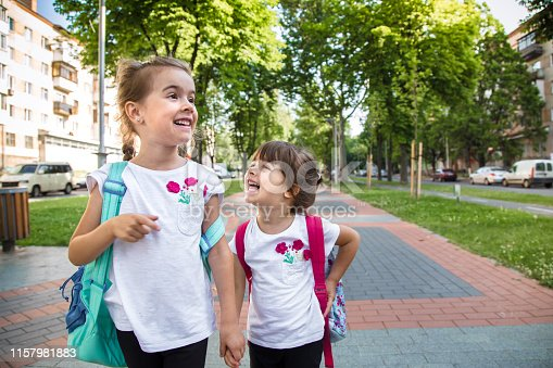 istock Back to school education concept with girl kids, elementary students, carrying backpacks going to class 1157981883