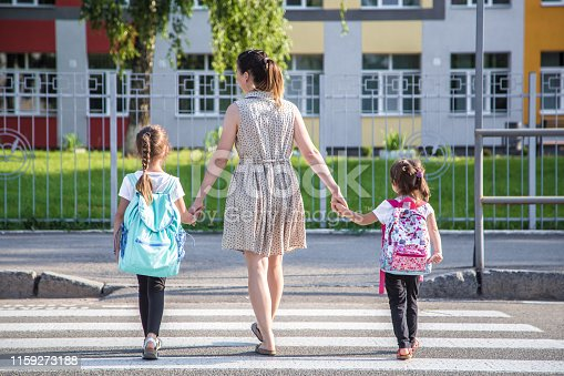 istock Back to school education concept with girl kids, elementary students, carrying backpacks going to class 1159273188