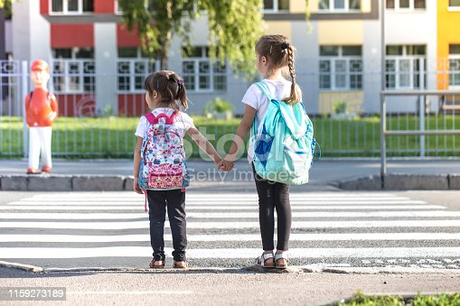 istock Back to school education concept with girl kids, elementary students, carrying backpacks going to class 1159273189