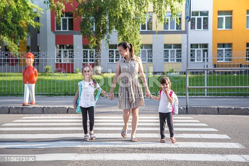 istock Back to school education concept with girl kids, elementary students, carrying backpacks going to class 1159273190