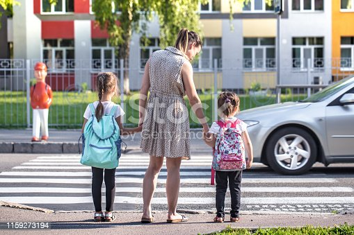 istock Back to school education concept with girl kids, elementary students, carrying backpacks going to class 1159273194