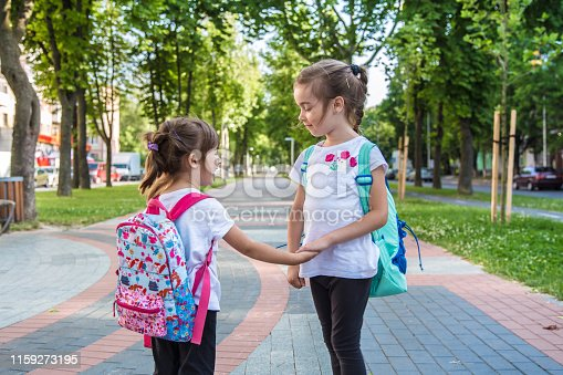 istock Back to school education concept with girl kids, elementary students, carrying backpacks going to class 1159273195