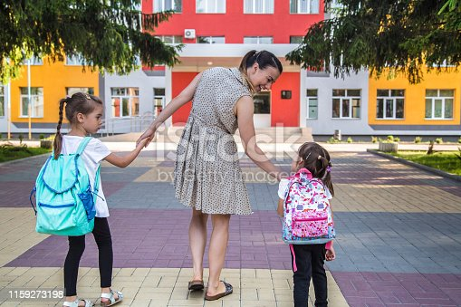 istock Back to school education concept with girl kids, elementary students, carrying backpacks going to class 1159273198