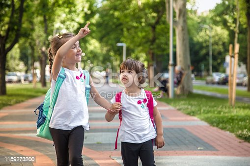 istock Back to school education concept with girl kids, elementary students, carrying backpacks going to class 1159273200