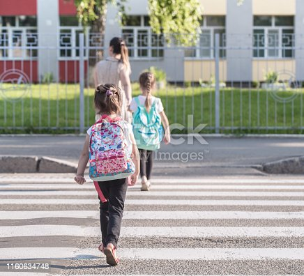 istock Back to school education concept with girl kids, elementary students, carrying backpacks going to class 1160634748