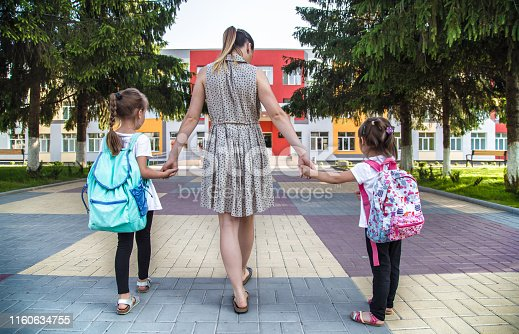 istock Back to school education concept with girl kids, elementary students, carrying backpacks going to class 1160634755