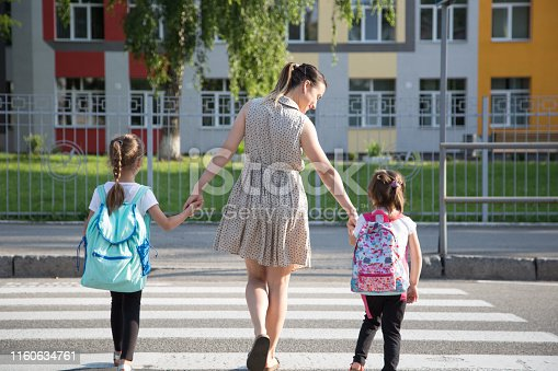 istock Back to school education concept with girl kids, elementary students, carrying backpacks going to class 1160634761