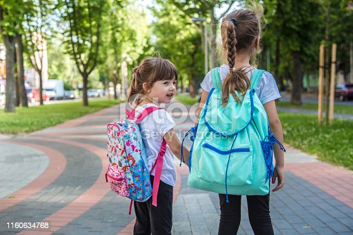 istock Back to school education concept with girl kids, elementary students, carrying backpacks going to class 1160634768