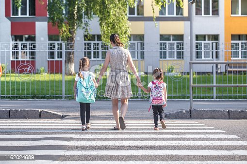 istock Back to school education concept with girl kids, elementary students, carrying backpacks going to class 1162024689