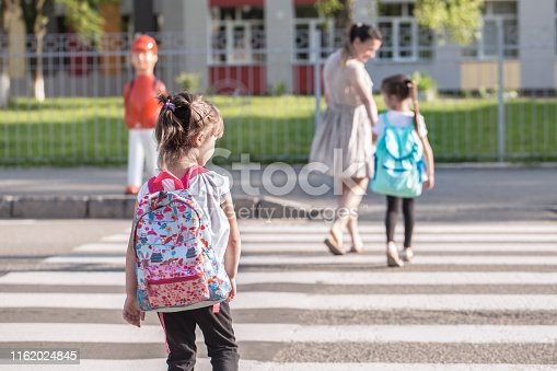istock Back to school education concept with girl kids, elementary students, carrying backpacks going to class 1162024845