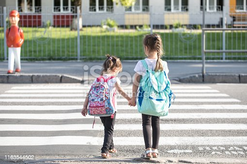 istock Back to school education concept with girl kids, elementary students, carrying backpacks going to class 1163544502