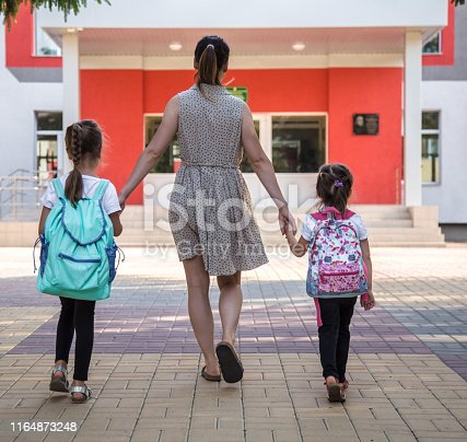 istock Back to school education concept with girl kids, elementary students, carrying backpacks going to class 1164873248