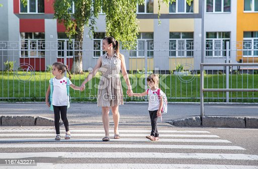istock Back to school education concept with girl kids, elementary students, carrying backpacks going to class 1167432271
