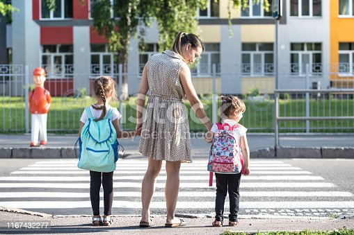 istock Back to school education concept with girl kids, elementary students, carrying backpacks going to class 1167432277