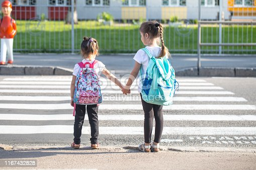 istock Back to school education concept with girl kids, elementary students, carrying backpacks going to class 1167432828