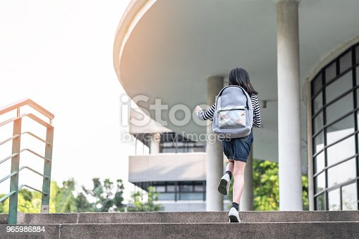 989255070istockphoto Back to school education concept with kid (elementary student girl) carrying backpacks going, running to class on school first day and walking up building stair happily 965986884