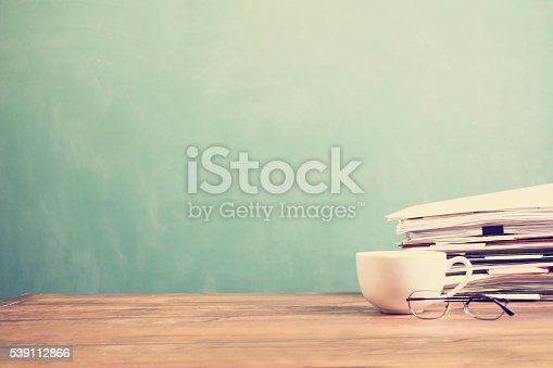 istock Back to school. Education. Papers stacked on desk. Chalkboard, coffee. 539112866