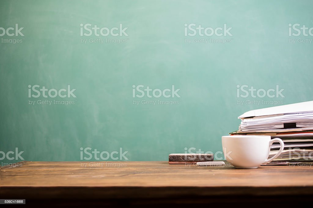 Back to school. Education. Papers stacked on desk. Chalkboard, coffee. royalty-free stock photo