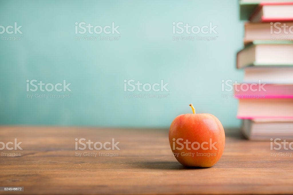 Back to school. Education. Textbooks, apple on desk. Chalkboard. stock photo