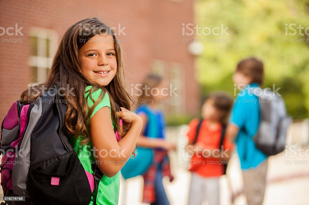 Back to School:  Elementary-age children, girl on school campus. стоковое фото