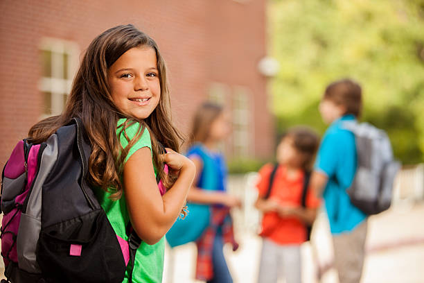 Back to School:  Elementary-age children, girl on school campus. stock photo