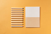 Notebook and coloring pencils on orange background. Back to school flat lay