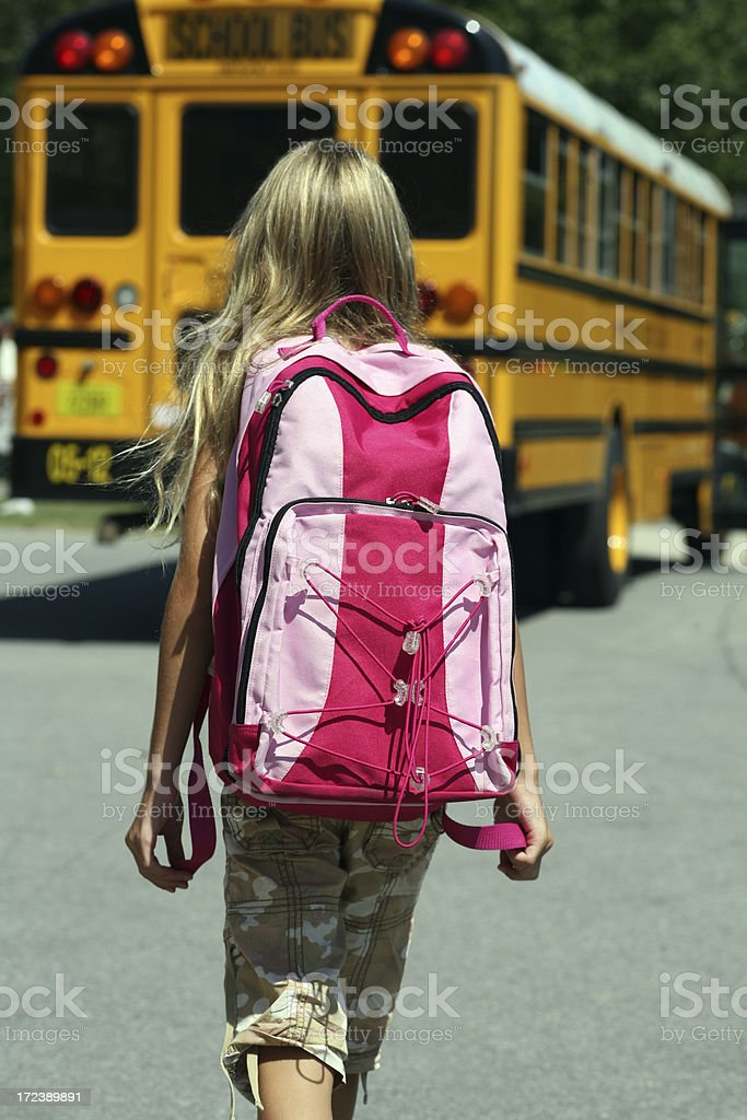 Back to School - Girl walking toward Bus stock photo