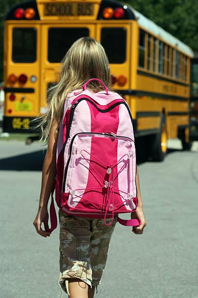 back to school-mädchen geht in richtung bus - camouflagekleidung mädchen stock-fotos und bilder